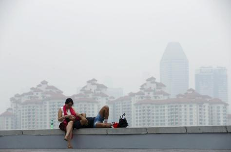 People rest in the backdrop of private residential estates shrouded by haze in Singapore October 25, 2015. Indonesia is preparing warships as a last resort to evacuate children and others suffering from smoke inhalation from slash-and-burn fires, a minister said on Friday, as the country struggles to contain fires expected to continue for weeks. Southeast Asia has suffered for years from annual